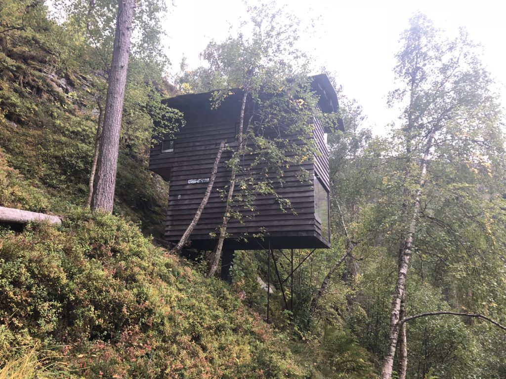 A small wooden cabin perched on a steep forested hillside