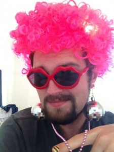 A bearded man in a bright pink wig that has three different disco-related light settings